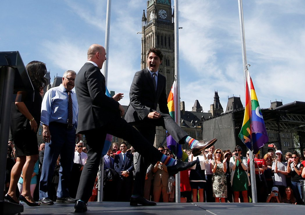 杜魯多(右)6月14日參加國會支持同性戀權利升旗活動,和國會議員一起展示彩虹襪。...