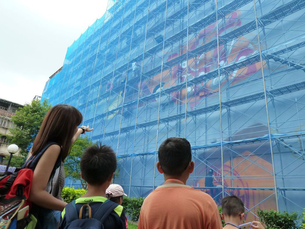 藝青會正於西門町再更新創作全台最大的塗鴉「這由我來」,引起民眾圍觀。 記者周志豪...