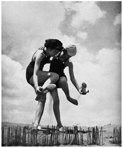 收錄在堀野正雄《女性美的攝影方法》一書中的照片──穿著泳裝的女性,正將鞋中細砂倒...