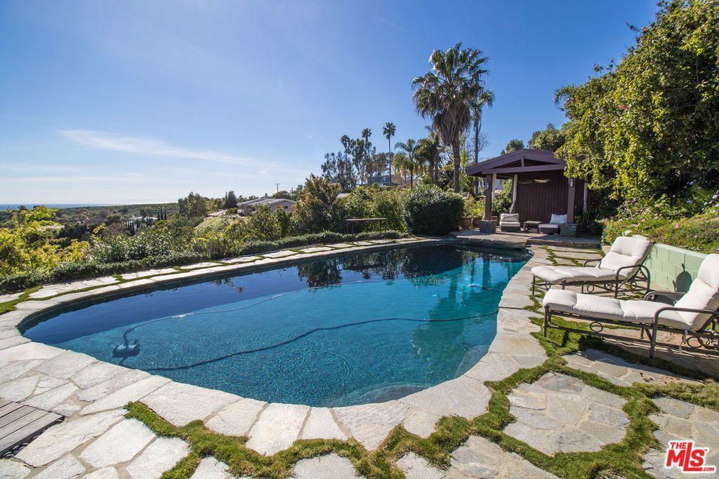 屋外有一間戶外廚房、迷你高爾夫球場、健身房、游泳池。(Realtor.com)