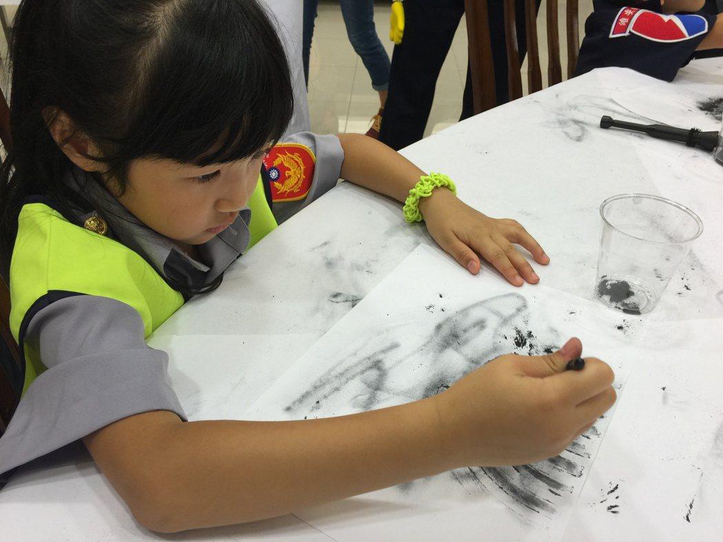 六歲的CSI體驗營學員翁婕恩在「小小福爾摩斯」關卡中,用碳粉刷出隱藏指紋。 記者...