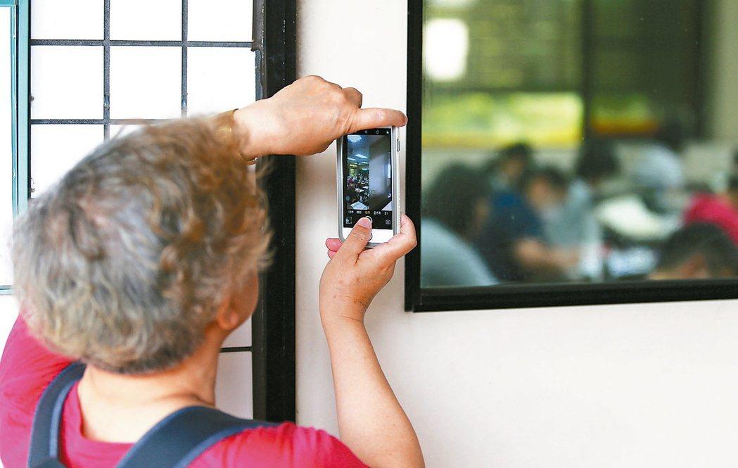 高普考登場,一位陪考的媽媽拿著手機拍攝在教室內看書子女的畫面。本報資料照/記者杜...