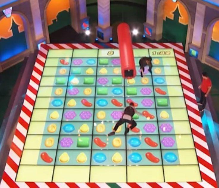 美國CBS電視網9日將推出《糖果傳奇》電視真人遊戲節目,參賽者穿戴吊具在大電視牆...