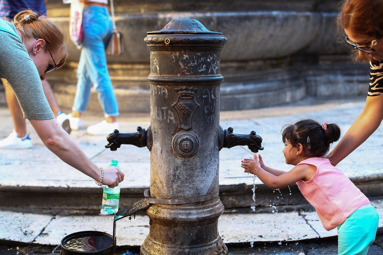 成人拿寶特瓶裝水,小女孩則洗手消暑。 (路透)