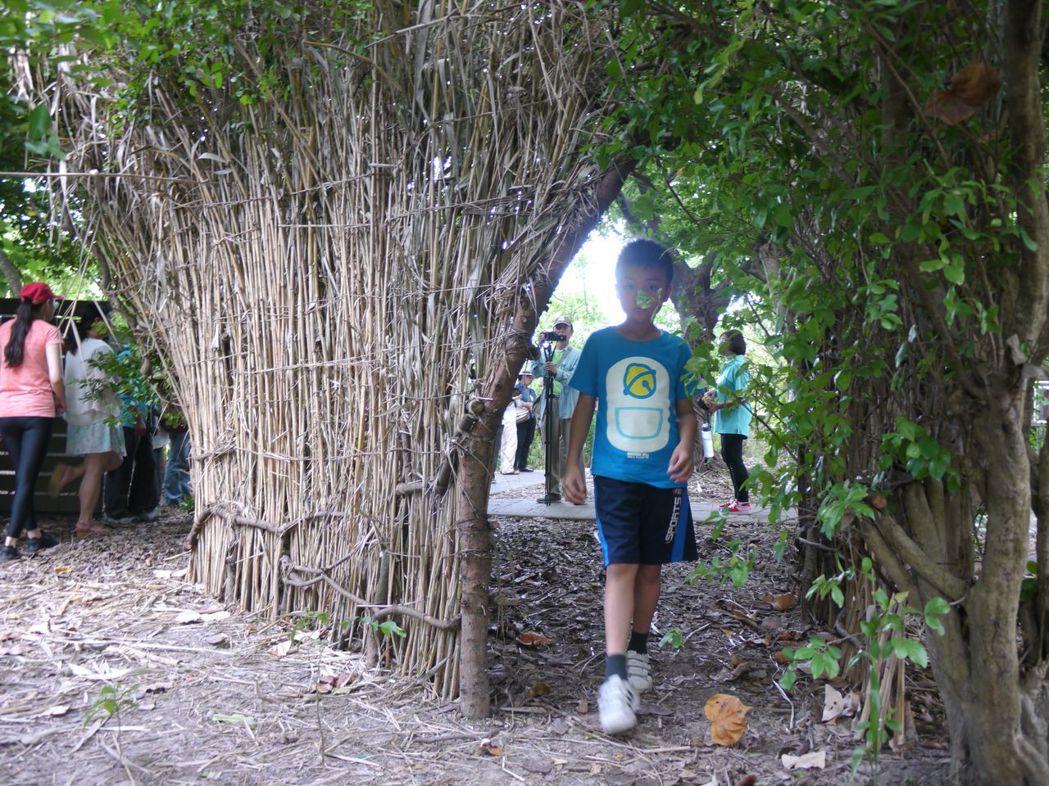 藝術家就地取材,撿拾鳥松濕地公園內的藤蔓與草梗等現地素材搭建圍籬,引領遊客放緩腳...