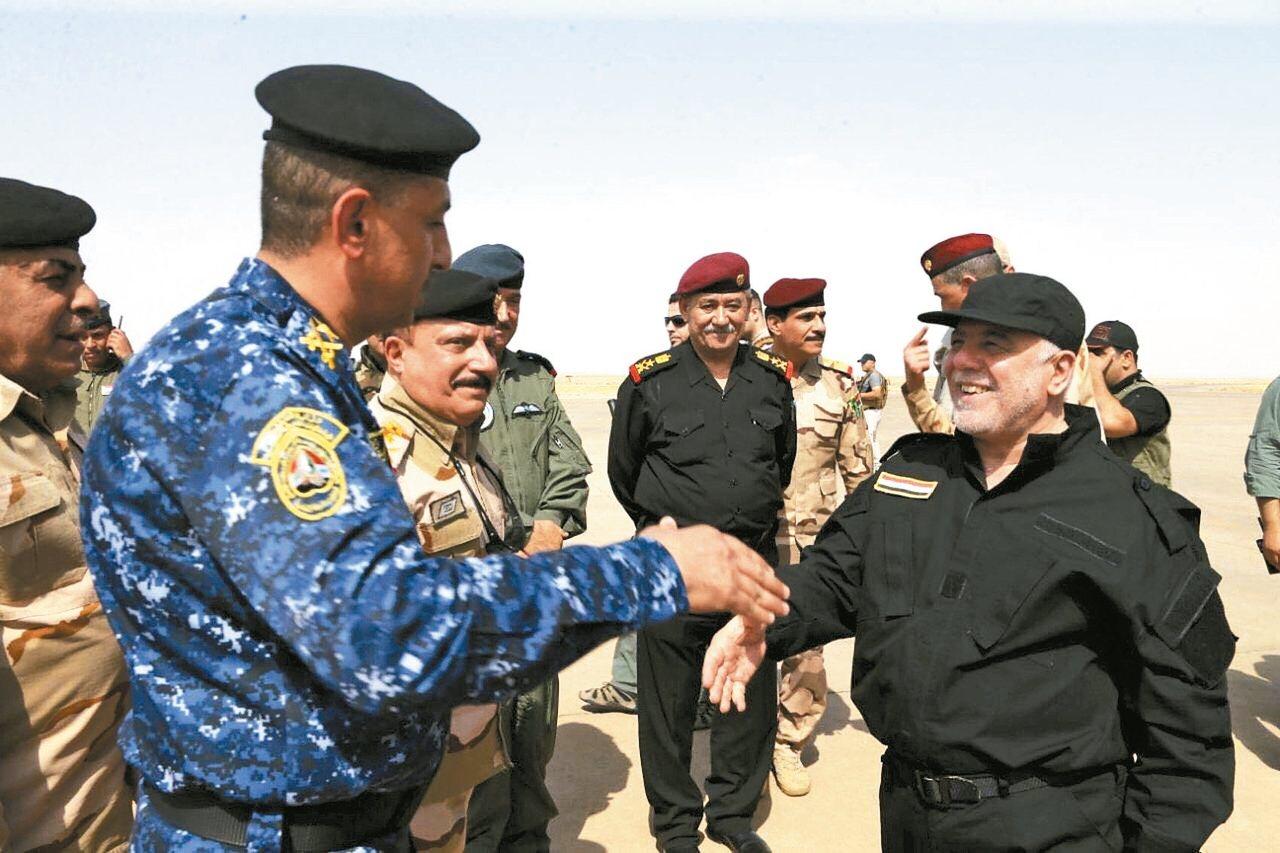 伊拉克總理阿巴迪(右)九日抵達摩蘇爾慰勉政府軍戰士。 路透