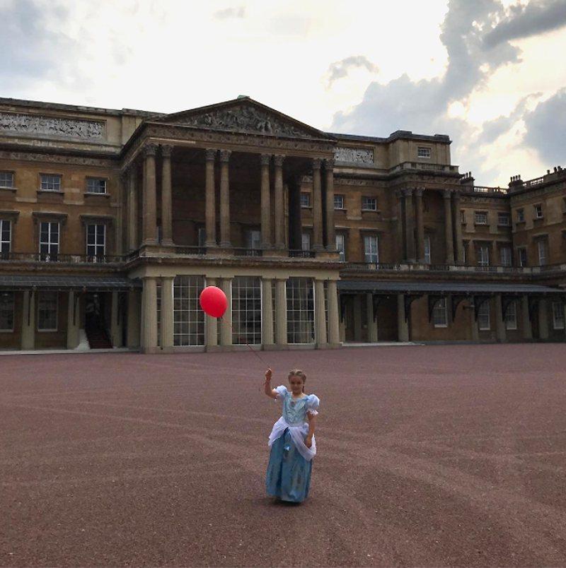 維多利亞.貝克漢貼出穿著公主服的哈波站在白金漢宮外面,手拿紅色汽球。 圖片來源/