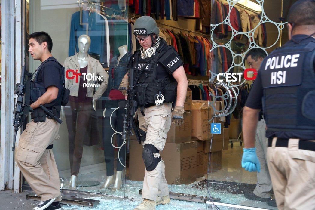 洛杉磯執法人員荷彈進入商圈時裝區,搜查為國際販毒集團洗錢謀利的商家。 (美聯社)