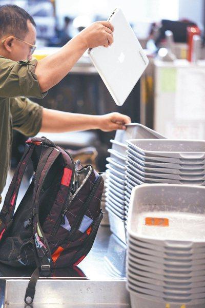 桃園機場出境旅客隨身行李安檢線,旅客將隨身攜帶的筆記型電腦放置X光機輸送帶上準備...