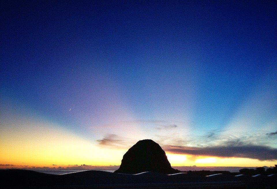 夕陽落在饅頭山後,形成另類的落日美景。(圖/顏子矞提供)