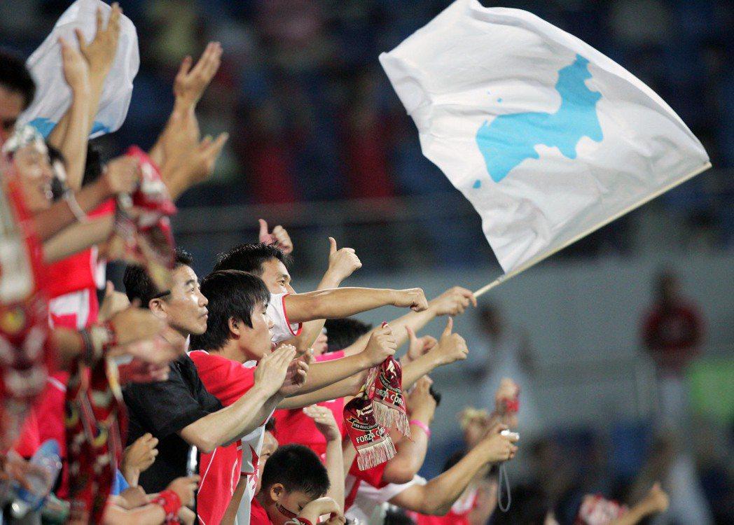 在場南韓民眾手持兩韓統一旗幟喝采。  圖/路透社