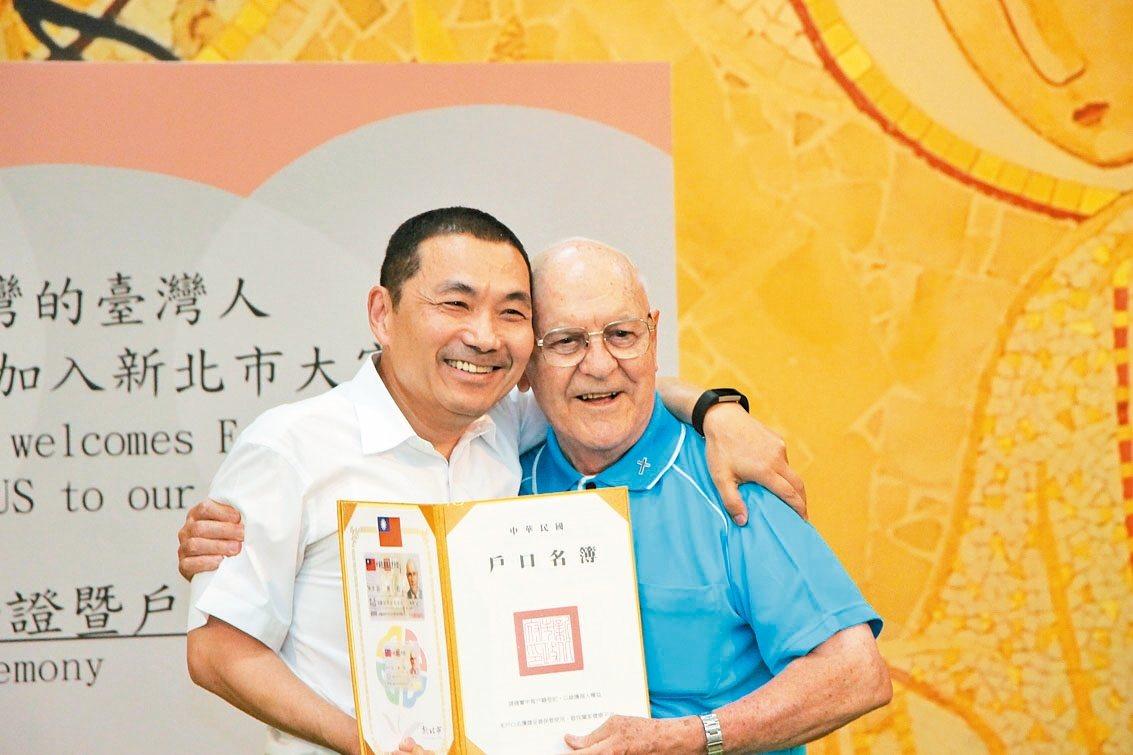 83歲神父谷寒松(右)關懷漢生病患,新北市副市長侯友宜(左)昨獻上身分證,谷寒松...