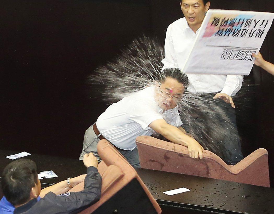 國民黨立委林為洲(左)丟出一顆水球直接砸中吳秉叡(中)眉心。記者陳柏亨/攝影