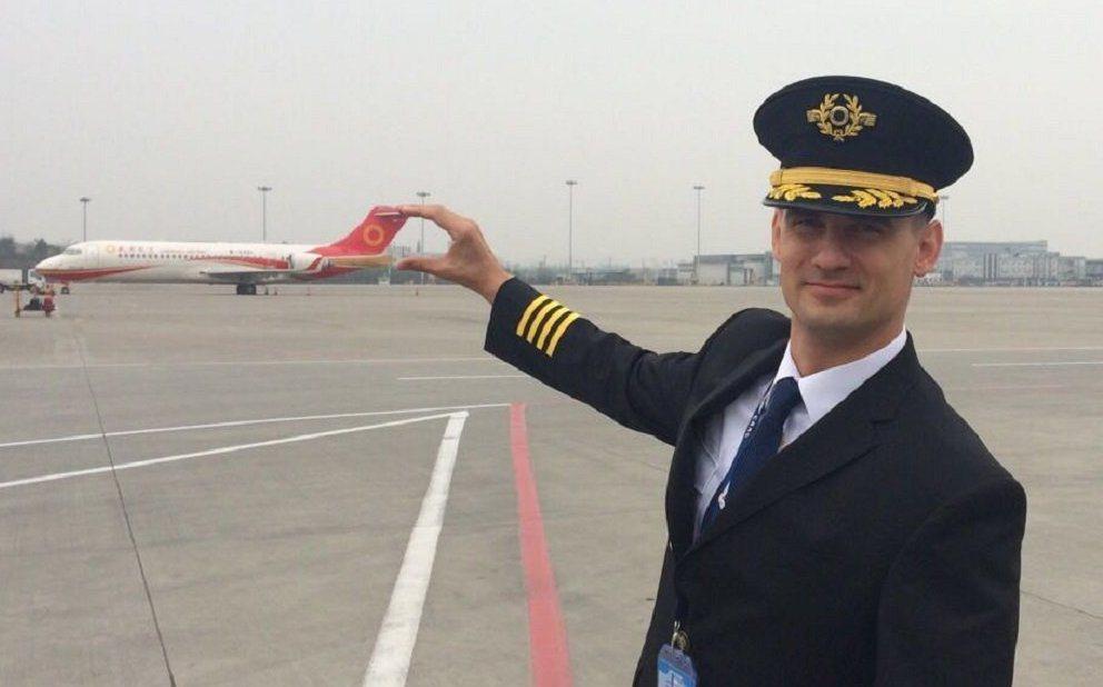 圖為俄國機師德米特裡·拉達耶夫,背景是成都航空的ARJ-21飛機。 圖/取自新華...