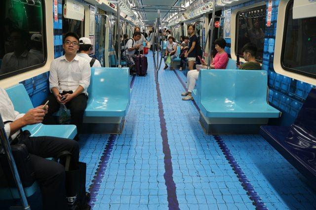 北捷車廂的世大運廣告,在地板鋪上泳池賽道圖案,逼真程度看起來就在水上行走。