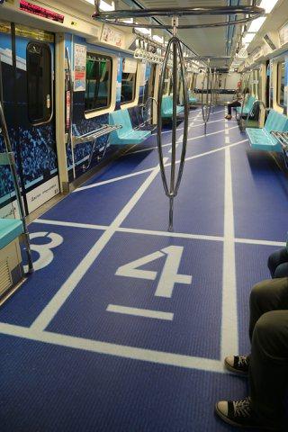 北捷車廂的世大運廣告,有田徑跑道。