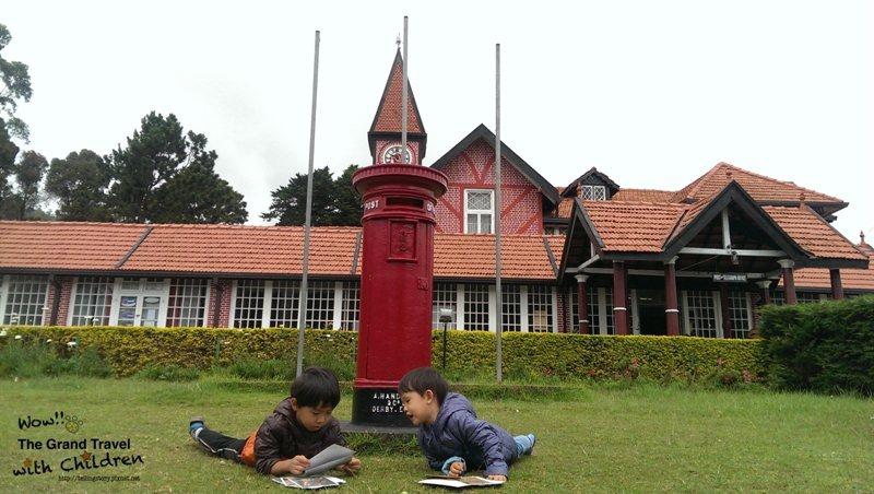 小孩在粉紅郵局草地上,欣賞明信片。攝影:吳怡慧Patti Wu
