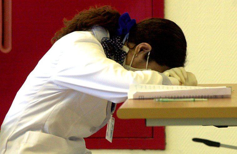醫護人員利用空檔,伏在桌上稍微補充體力。 本報資料照片