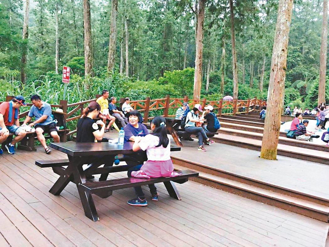 溪頭園區在木椅上加裝橫板,也在草皮區增設木桌,提供遊客坐著休息不必橫躺了。 記者黑中亮/攝影