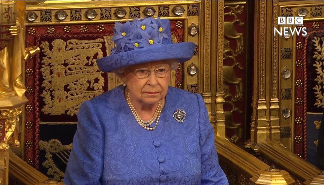 英國女王伊麗莎白二世6月21日發表國會開議演說時,戴了一頂神似歐盟旗的帽子,在社...