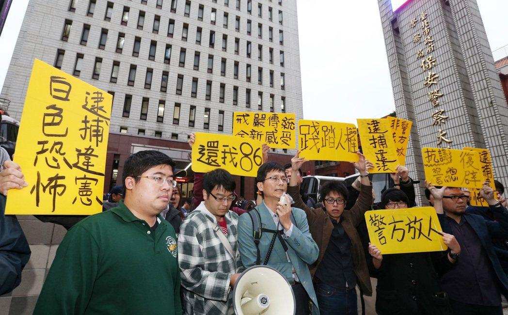 2014年,律師詹順貴(中)及支持者,在台北市保安大隊門口,高舉標語聲援涉嫌妨害...