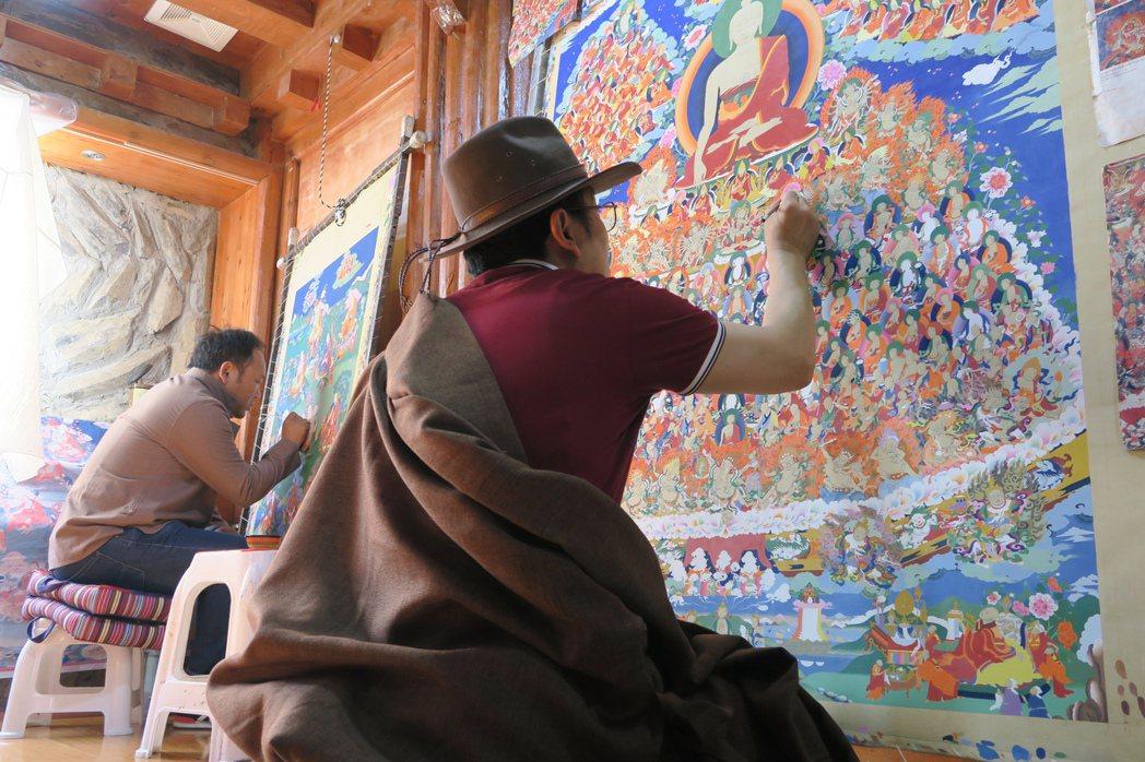 唐卡作畫是「修心」,作畫者每天得畫8至9小時,且按傳統不能坐椅子。圖右為師傅曲久...