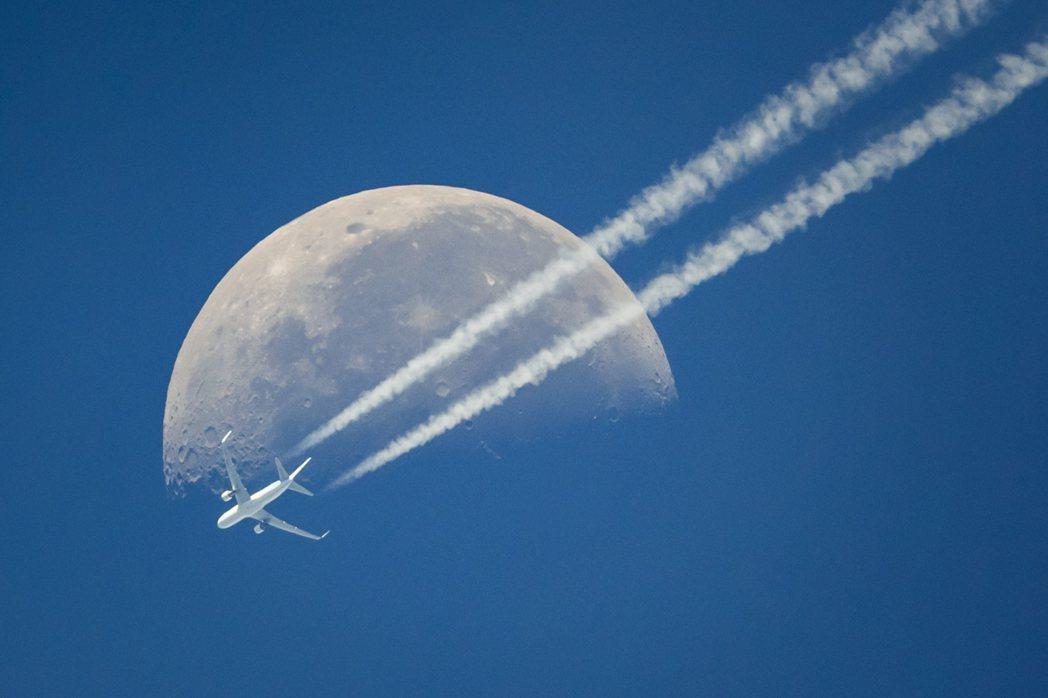 一架飛機飛越瑞士日內瓦,與天空中的月亮相映成趣。 美聯社
