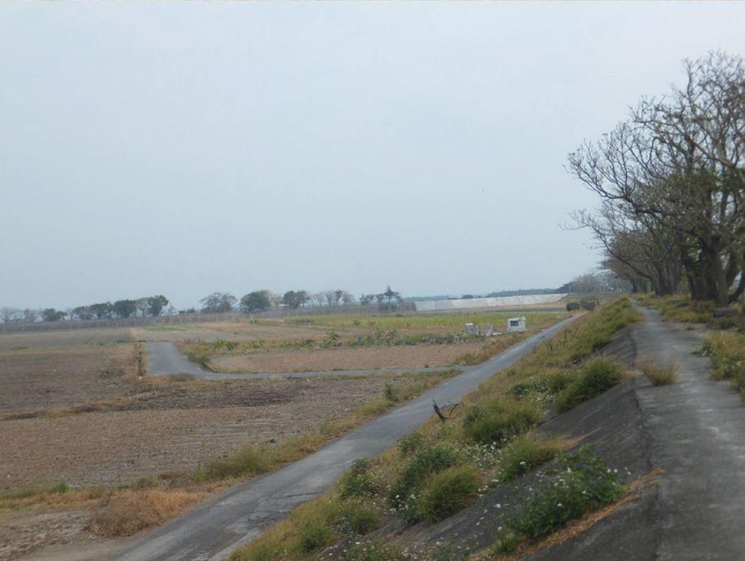 照片中位在曾文溪堤防外白色屋體,原是黃梱條老家水患遷村前的居所所在,今已為耕地。