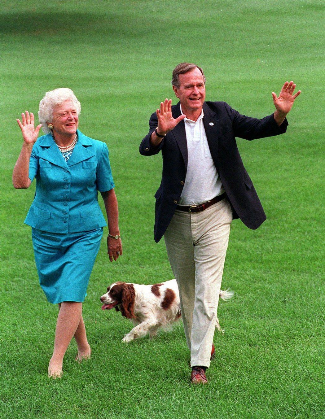 美國前總統老布希夫婦1992年和寵物犬米莉走過白宮草坪。美聯社 美聯社