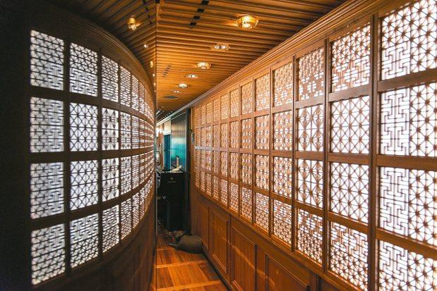 Lounge「藍月亮」入口的組子燈箱壁面,映照在如鏡面的烤漆牆上形成了兩側組子輝...