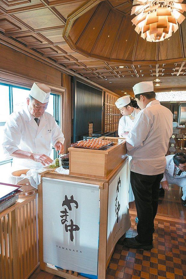 70幾歲的山中主廚在晃動的空間中、狹窄的工作台上,神情嚴肅的為九州七星的客人捏壽...