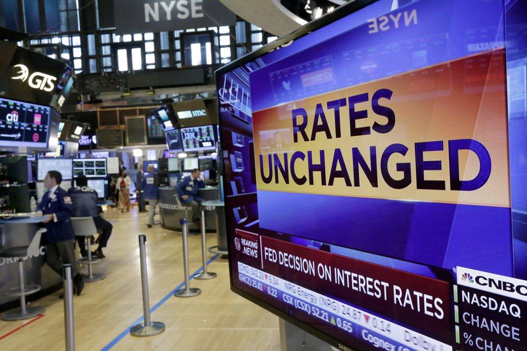 美國紐約證券交易所的電視螢幕內容顯示,聯準會委員一致通過利率維持不變。 美聯社資...