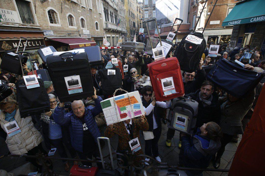 「威尼斯的出埃及記」:抗議觀光客擾亂生活的威尼斯人,舉起行李箱象徵準備離開威尼斯...