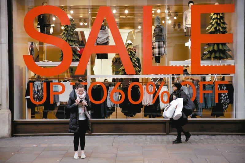 英國物價上漲,加薪速度卻跟不上,許多人不敢放手消費。圖為倫敦知名購物街「牛津街」的商店櫥窗貼出商品打折的廣告。 路透