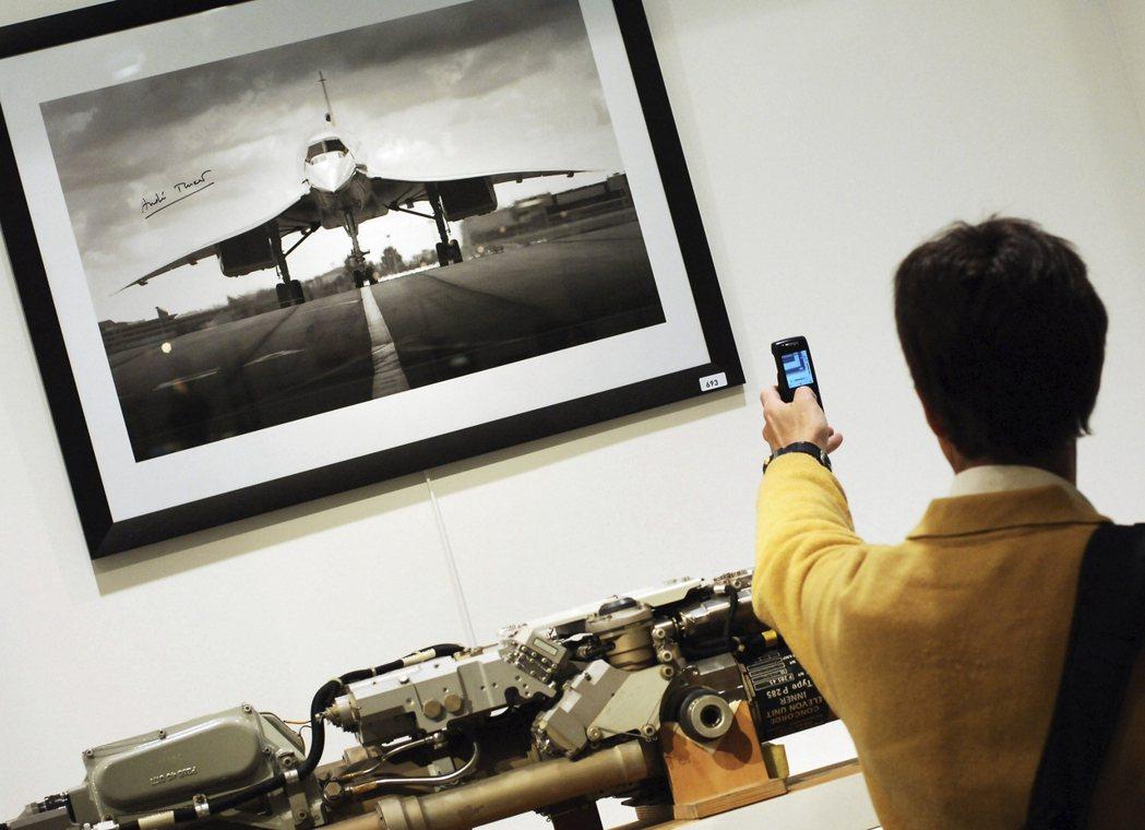 一名男子持手機拍下協和號的黑白照片。 美聯社