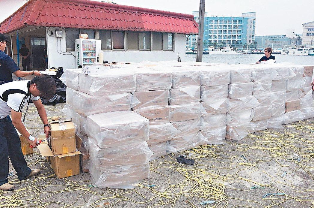 警方及海巡人員在屏東東港查扣高雄籍「皇星壹號」涉嫌走私一百九十八箱香菸。 記者林保光/翻攝