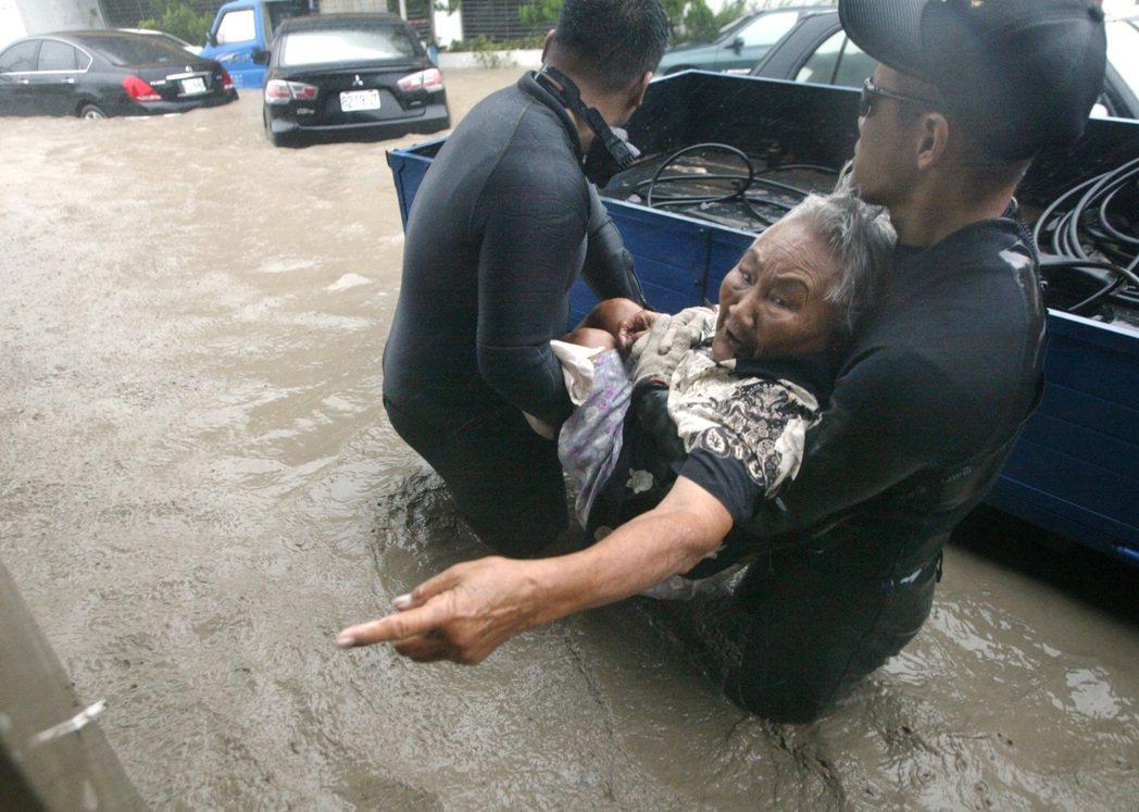 2009年,莫拉克颱風侵襲台灣,造成南部大淹水,二位救援人員抬著一位老太太到安全...