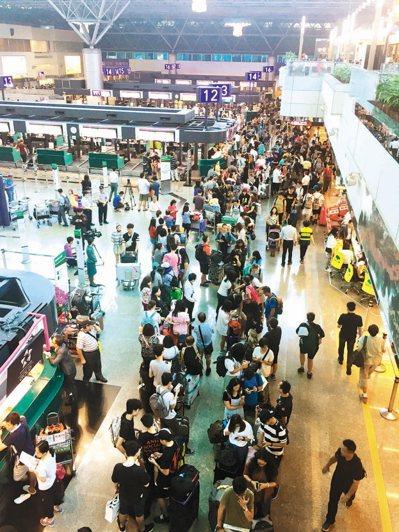 長榮航空取消50個來回航班,旅客擠爆桃園機場。 中央社