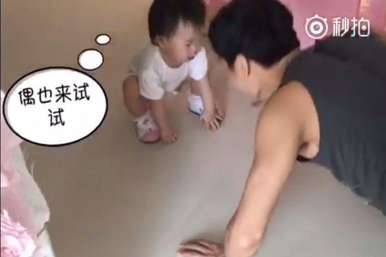 米粒蹲在地上,爸爸秦昊則在一旁做伏地挺身。 圖/擷自伊能靜秒拍視頻