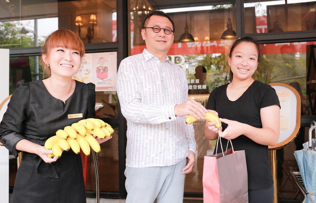 雄崗建設董事長林清吉(中)贈送香蕉給來「Eagle義來藝去」餐廳消費的民眾。 攝...
