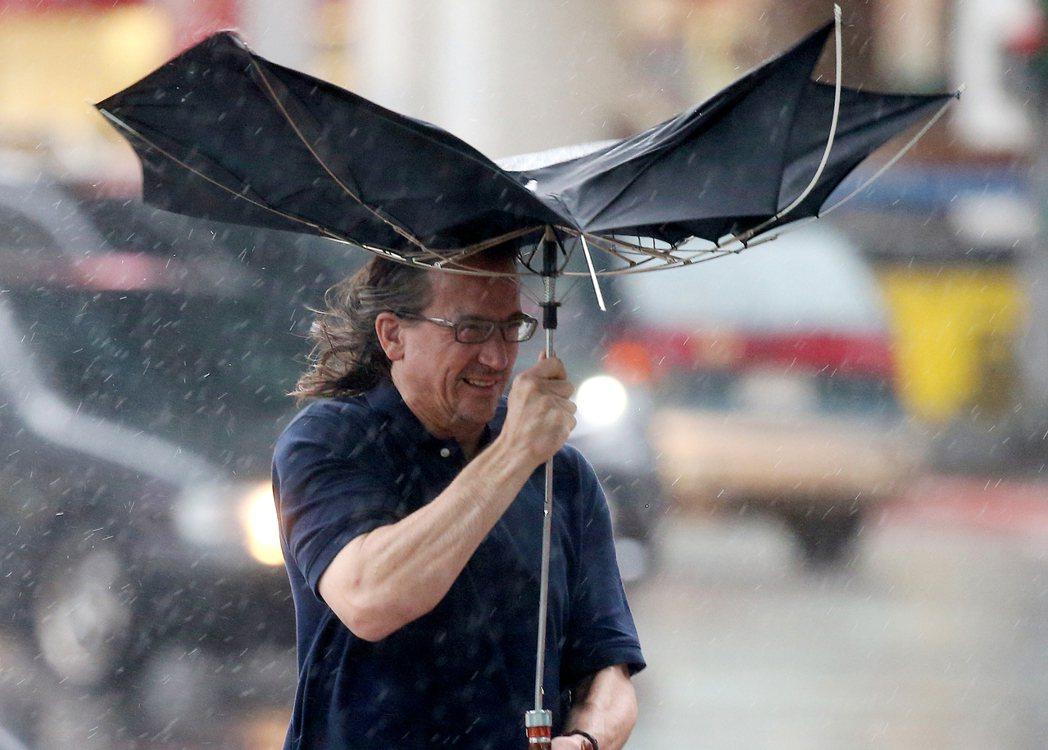 尼莎颱風襲台,台北市昨天傍晚風雨漸強,路上行人撐著傘遮雨,但手中的傘被突如其來的...