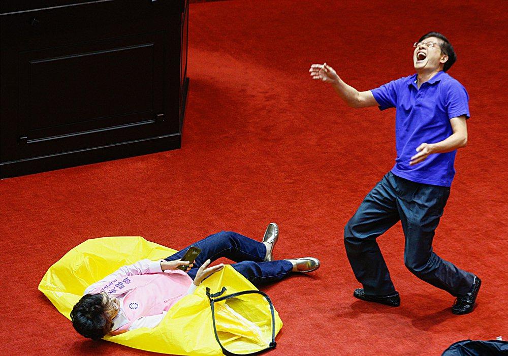 國民黨立委黃昭順(左)要躺在充氣睡墊上,卻不慎跌倒,一旁的立委羅明才(右)大笑。...