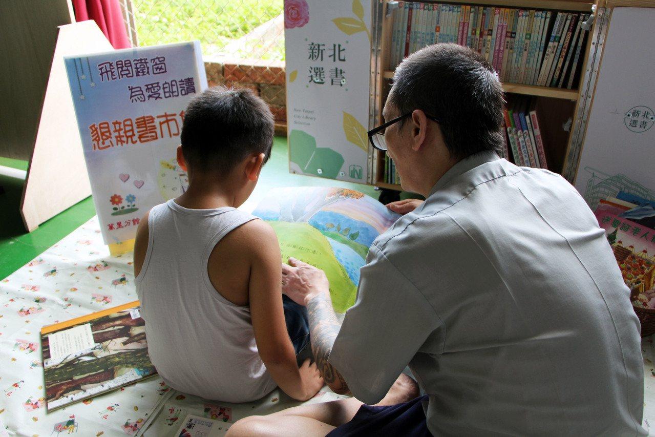 基隆監獄昨舉辦懇親會,受刑人和小孩一同閱讀童書。 圖/新北圖書館提供