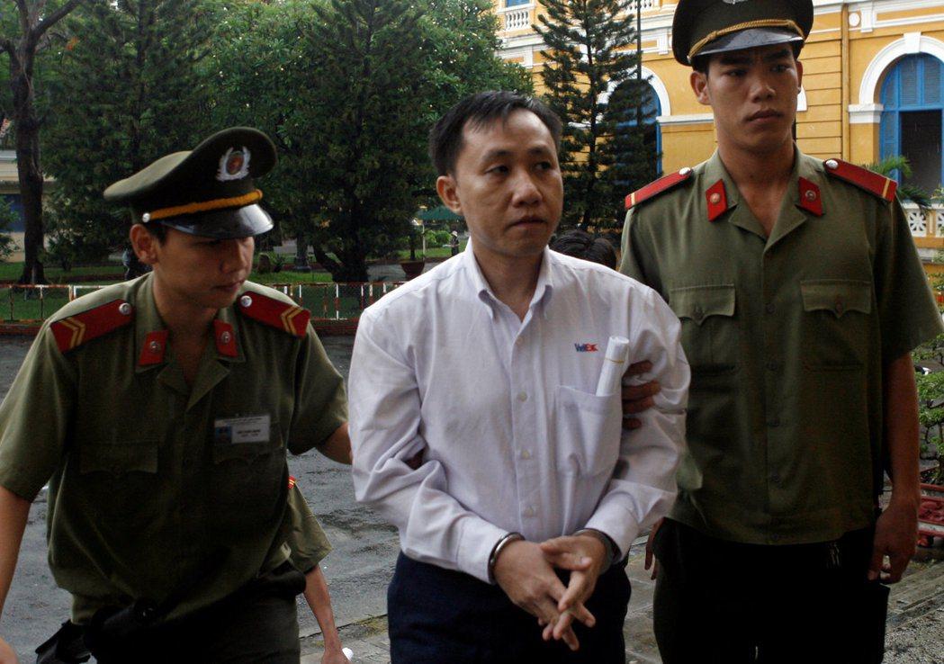 39歲的維權人士阮北傳(中)在警察押解下,上銬出庭應訊。  (路透)