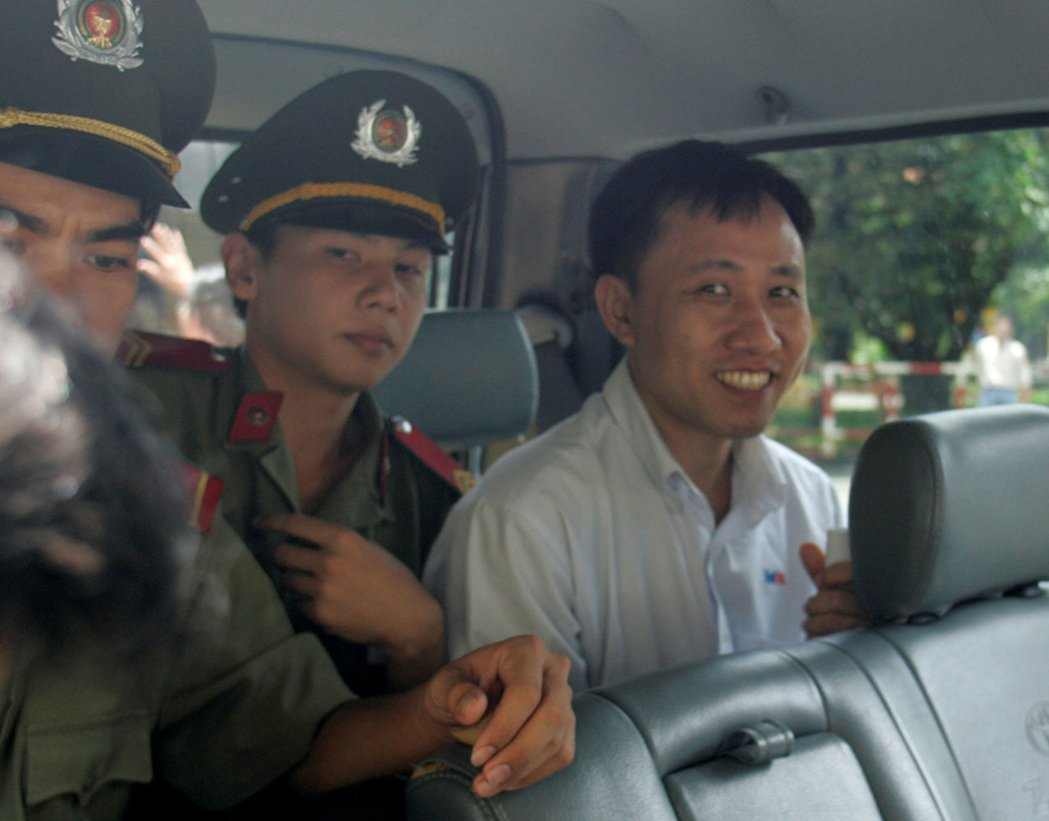 維權人士阮北傳(右)被指控從事反共宣傳罪,他離開法庭後被帶上警車。  (路透)