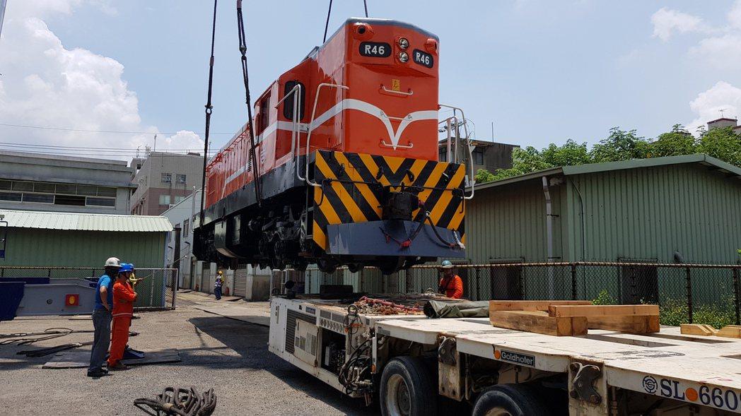 R46柴電機車頭吊掛上板車,晚間將運送到功維敘隧道南口附近預舖的軌道放置。記者黃...