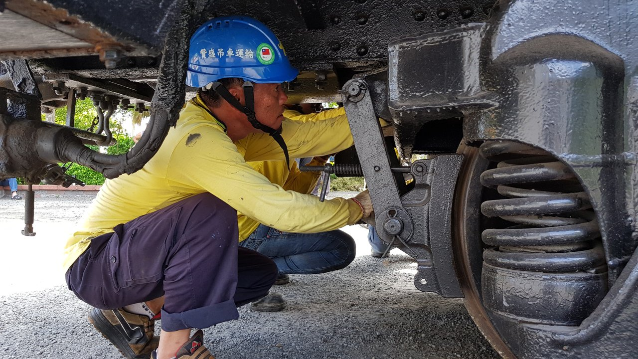吊掛空間狹小,工人鑽進車底下作業。記者黃瑞典/攝影