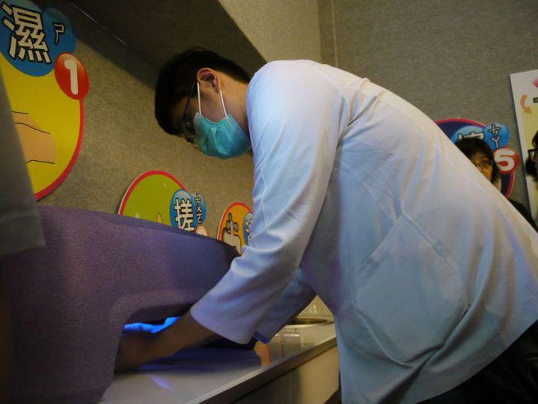透過手部螢光檢測儀,可檢測漂白水的消毒之功效。 記者徐白櫻/攝影