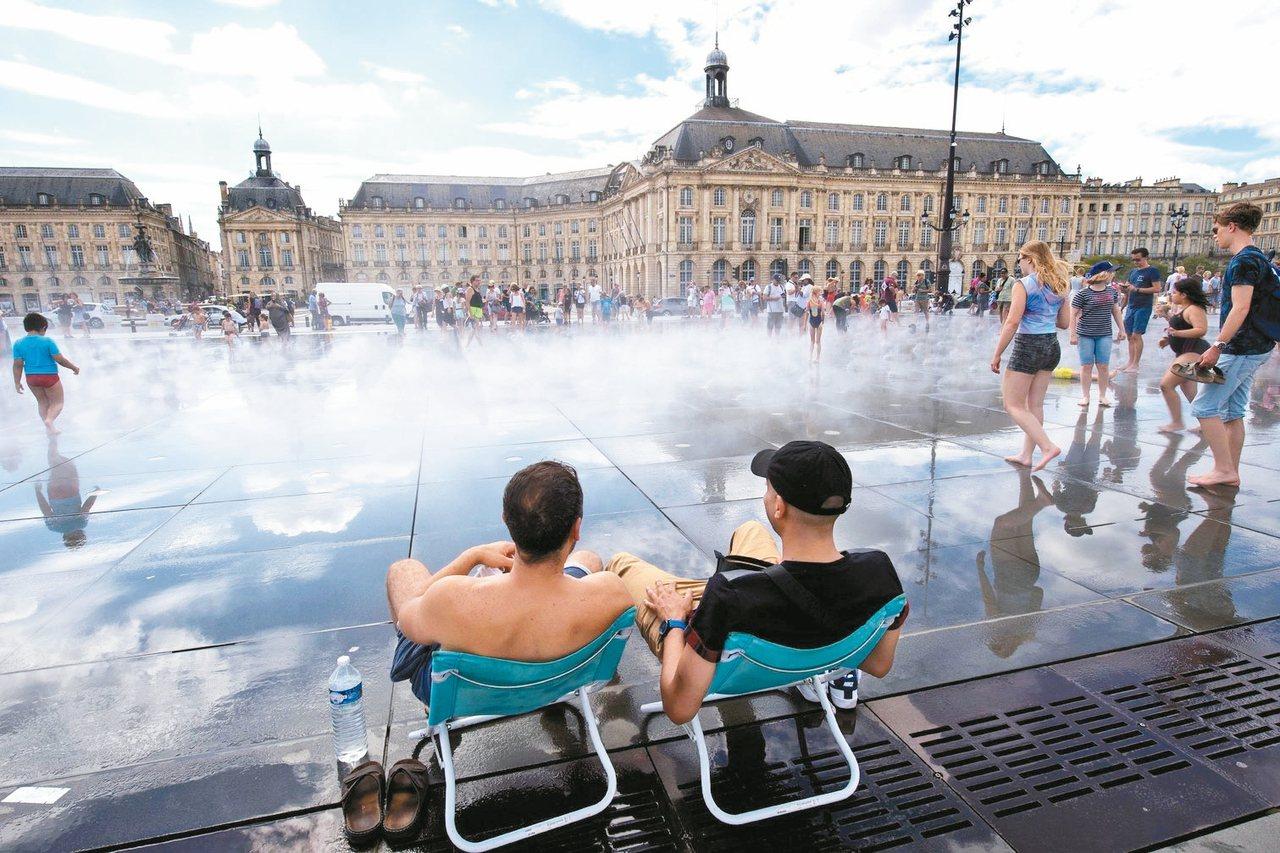 氣溫飆破攝氏40度,法國波爾多的民眾在廣場戲水消暑。面對氣候變遷在歐洲造成的致命...