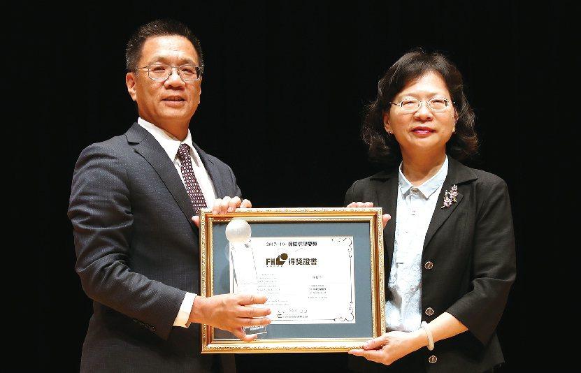 富邦人壽總經理陳俊伴(左)從金管會保險局局長李滿治手中,接下最佳保險領導人獎,三...
